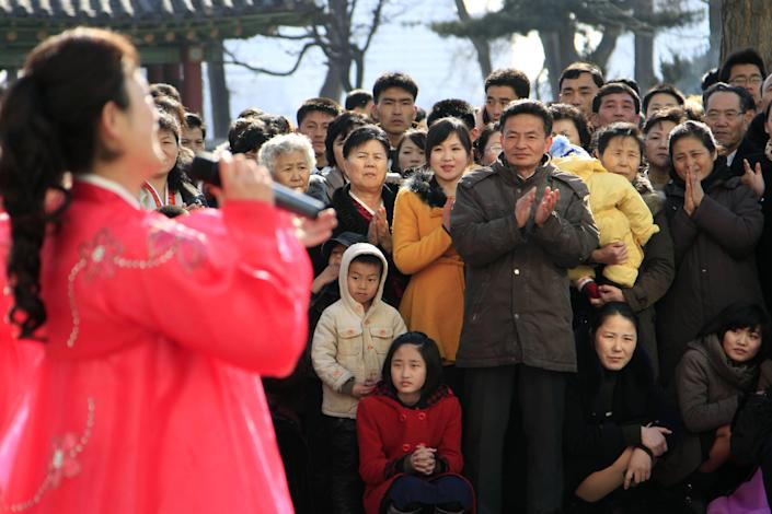People gather to watch a performer sing near an election site in the Central District near Taedong Gate, in Pyongyang, North Korea, Sunday, March 9, 2014. North Korean voters went to polling stations to elect a new national legislature, although they don't get to choose who to vote for since there is only one candidate per district. (AP Photo/Kim Kwang Hyon)