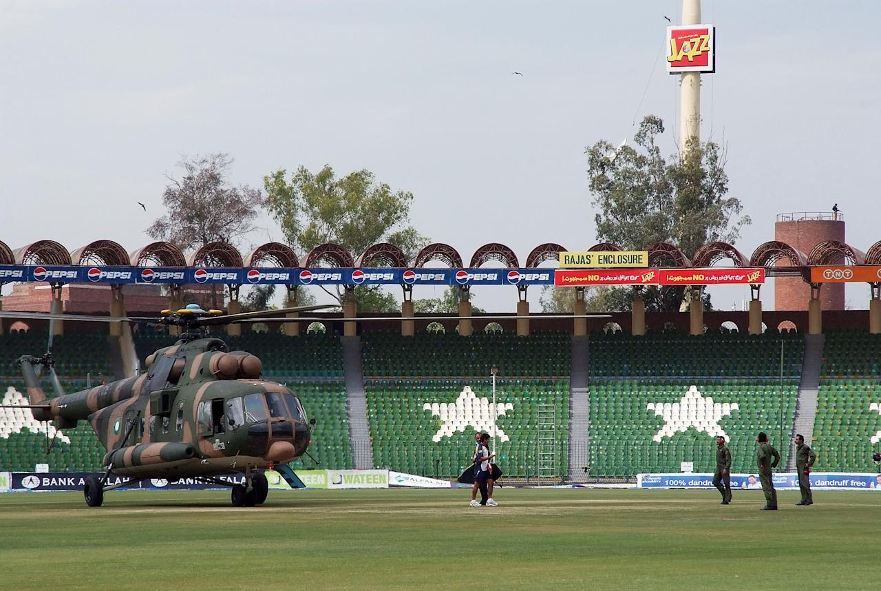 LAHORE, PAKISTAN - MARCH 03:  A member of the Sri Lankan international cricket team prepares to board a rescue helicopter as air crew look on at the Gadaffi Stadium on March 3, 2009 in Lahore, Pakistan. The team were attacked in a coach as it travelled through the heart of Lahore, leaving five Pakistani policeman dead and several team members injured. (Photo by Lee Austin/Getty Images)