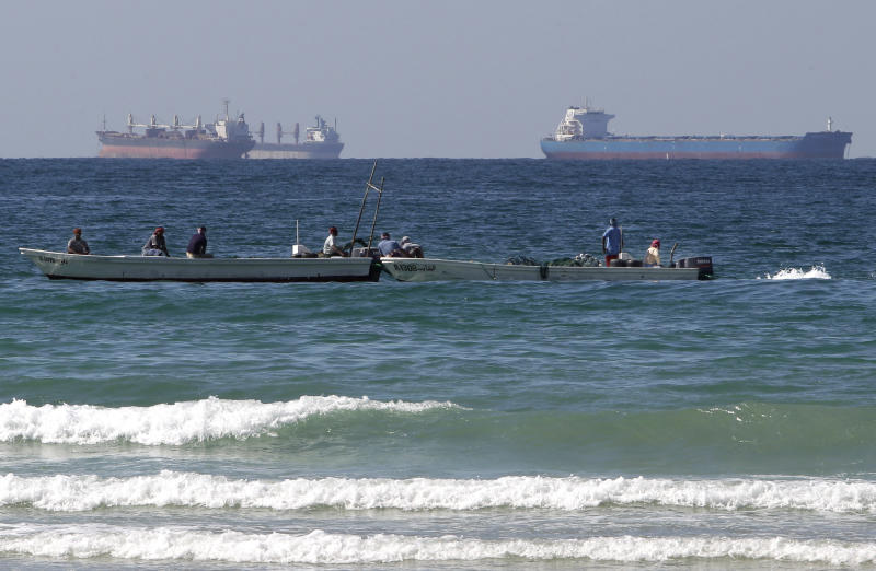 FILE - In this Thursday, Jan. 19, 2012 file photo, fishing boats are seen in front of oil tankers on the Persian Gulf waters, south of the Strait of Hormuz, off the shores of Ras Al Khaimah in the United Arab Emirates. Sometime later this year, the U.S. Navy plans to send minesweepers and warships into the Gulf for exercises intended to make Iran think twice about any attempts to block oil tanker traffic through the narrow waterway that links the region's huge oil fields with world markets. (AP Photo/Kamran Jebreili, File)