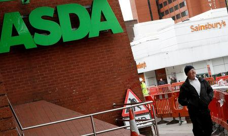 A man walks past branches of ASDA and Sainsbury's in Stockport, Britain April 30, 2018. REUTERS/Phil Noble/Files