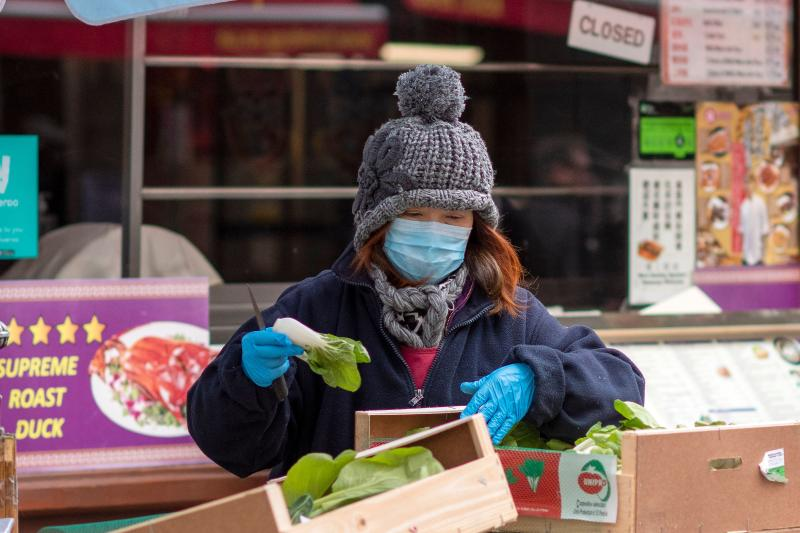 A worker wears a surgical face mask as she prepares vegetables on a stall in London's China Town district.