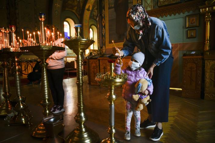A woman and her child, wearing face masks to protect against coronavirus, light candles after a Great Saturday Mass in a church in Simferopol, Crimea, Saturday, April 18, 2020. For Orthodox Christians, this is normally a time of reflection, communal mourning and joyful release, of centuries-old ceremonies steeped in symbolism and tradition. But this year, Easter - by far the most significant religious holiday for the world's roughly 300 million Orthodox - has essentially been cancelled. (AP Photo)