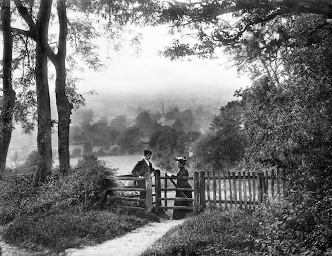 A couple in the Cotswolds negotiate a kissing gate - Credit: Historic England Archive/Heritage Images