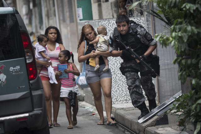 "After hearing gun shots, a military police officer runs for cover, past residents, during an operation in the Mare slum complex, ahead of its ""pacification,"" in Rio de Janeiro, Brazil, Tuesday, March 25, 2014. Elite federal police and army troops will be sent to the city to help quell a wave of violence in so-called ""pacified"" slums. Recent attacks on police bases in the favelas is raising concerns about an ambitious security program that began in 2008, in part to secure the city ahead of this year's World Cup and the 2016 Olympics. (AP Photo/Felipe Dana)"