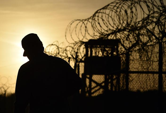 """An April 9, 2014 photo taken during an escorted visit and reviewed by the US military shows a US soldier walking next to the razor wire-topped fence at the abandoned """"Camp X-Ray"""" detention facility at the US Naval Station in Guantanamo Bay, Cuba (AFP Photo/Mladen Antonov)"""