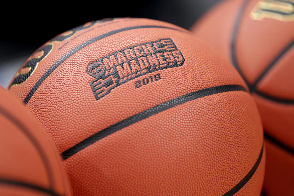 FILE - In this, March 20, 2019, file photo, a basketball with March Madness 2019 logo sits in a rack before Michigan's practice at the NCAA college basketball tournament in Des Moines, Iowa. All 30 college conferences are still planning to hold basketball tournaments where the winner earns the automatic bid to the NCAAs. But the leagues also have until Feb. 26, 2021, to notify the selection committee if there will be any changes to how the automatic bid is awarded. (AP Photo/Nati Harnik, File)