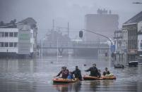 People use rubber rafts in floodwaters after the Meuse River broke its banks during heavy flooding in Liege, Belgium, Thursday, July 15, 2021. Heavy rainfall is causing flooding in several provinces in Belgium with rain expected to last until Friday. (AP Photo/Valentin Bianchi)