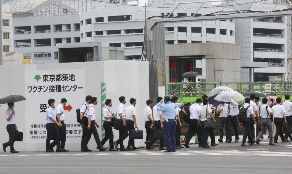 Police officers and firefighters arrive to receive the Moderna coronavirus vaccine at a former Tsukiji fish market which was turned to be a temporary mass vaccination center site set up by Tokyo metropolitan government in Tokyo Wednesday, June 16, 2021. (AP Photo/Koji Sasahara)