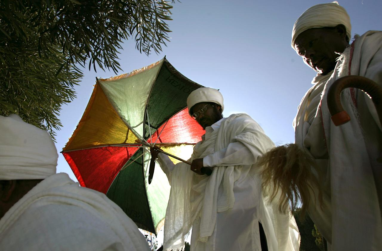 Ethiopian Jewish man uses an umbrella to protect himself from the sun during the prayer of the Sigd holy day on a hill overlooking Jerusalem, Thursday, Dec. 1, 2005. The prayer is performed by Ethiopian Jews every year to celebrate their community's connection and commitment to Israel. About 80,000 Ethiopian Jews live in Israel, many of them came in massive Israeli airlifts during times of crisis in Ethiopia in 1984 and 1991.  (AP Photo/Emilio Morenatti)