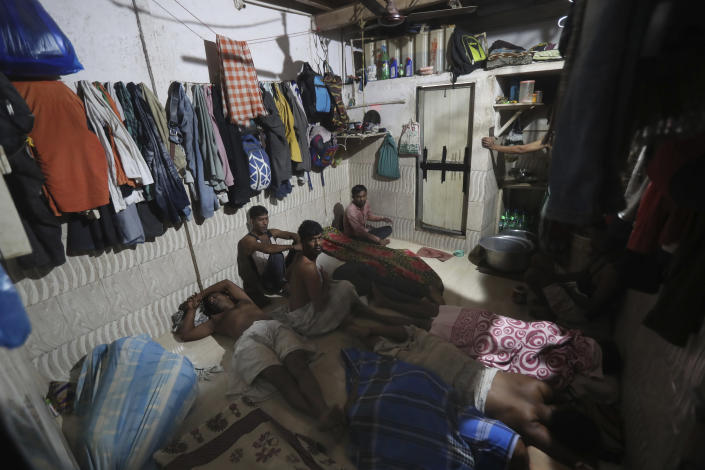 Migrant laborers from state of West Bengal, who recently returned back to Mumbai, India, sit together in their shared room as they wait for their turn for the restroom, Tuesday, Nov. 23, 2020. (AP Photo/Rafiq Maqbool)