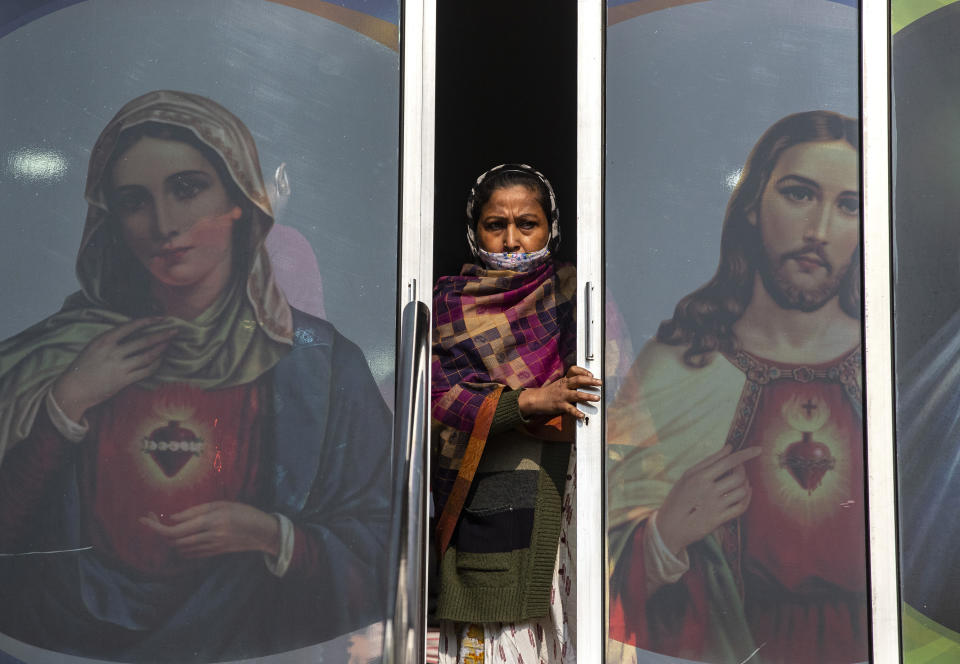 A Christian woman partially wearing a face mask as a precaution against the coronavirus leaves after attending a Christmas mass at a church in Gauhati, India, Friday, Dec. 25, 2020. (AP Photo/Anupam Nath)