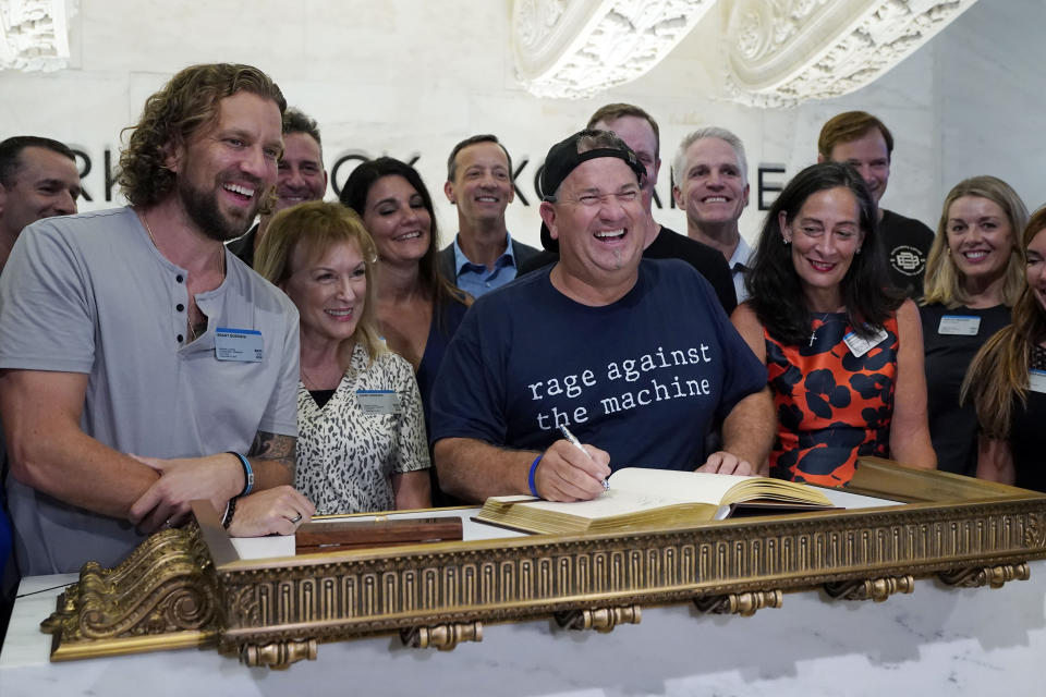 Dutch Bros Coffee Co-founder and Executive Chairman Travis Boersma, center, poses for photos as he signs the New York Stock Exchange guest book, before ringing the closing bell, Wednesday, Sept. 15, 2021. (AP Photo/Richard Drew)