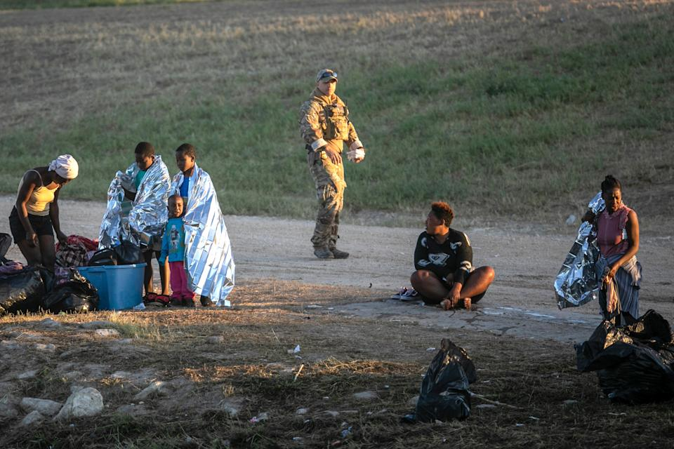 A U.S. Border Patrol agent on Thursday passes Haitian immigrant families who have crossed the Rio Grande to Del Rio, Texas, from Ciudad Acuna, Mexico.
