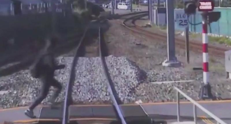A pedestrian rushes in front of a train at a crossing in New Zealand.