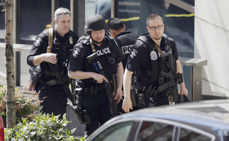 Seattle Police officers walk with guns near the scene of a shooting involving several police officers in downtown Seattle, Thursday, April 20, 2017. (AP Photo/Ted S. Warren)