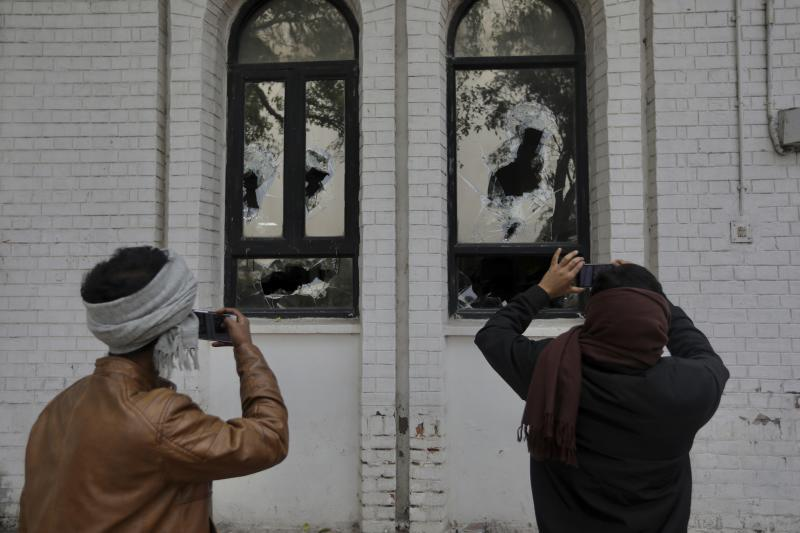 Students take photographs broken windows of the Jamia Millia Islamia University library that was stormed by police Sunday in New Delhi, India, Monday, Dec.16, 2019. Police on Sunday fired tear-gas and struck with batons  students who protested against a new law that will give citizenship to non-Muslims fleeing religious persecution from several neighboring countries. (AP Photo/Manish Swarup)