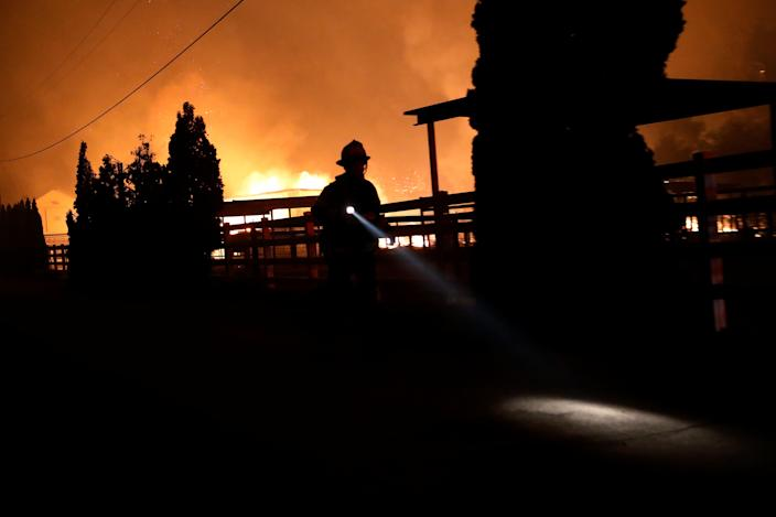 A firefighter runs along a dirt road during the wind-driven Kincade Fire in Windsor, California, Oct. 27, 2019. (Photo: Stephen Lam/Reuters)