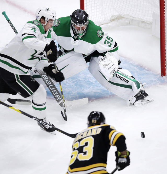 Dallas Stars goaltender Anton Khudobin (35) watches as Boston Bruins left wing Brad Marchand (63) chases the puck during the first period of a hockey game in Boston, Monday, Nov. 5, 2018. At left is Dallas Stars defenseman Miro Heiskanen (4). (AP Photo/Charles Krupa)