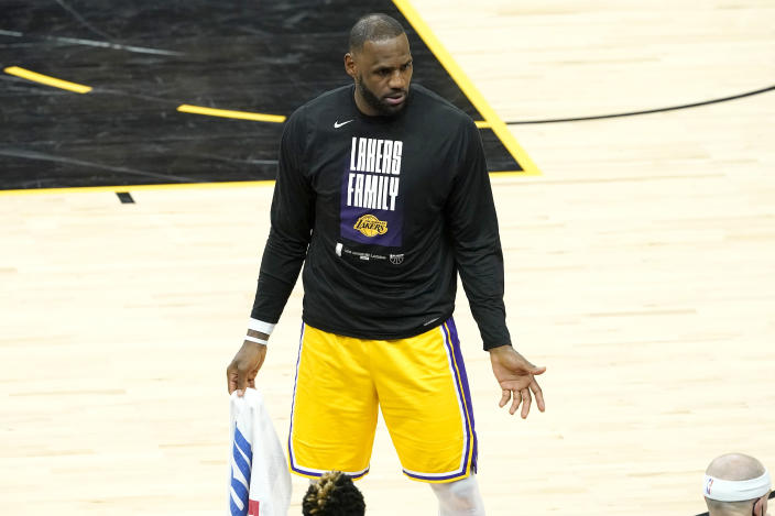 Los Angeles Lakers forward LeBron James speaks to his teammates on the bench during the second half of Game 5 of an NBA basketball first-round playoff series against the Phoenix Suns, Tuesday, June 1, 2021, in Phoenix. (AP Photo/Matt York)