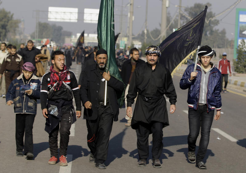 Shiite pilgrims march to Karbala for the Arbaeen celebration in Baghdad, Iraq, Monday, Dec. 31, 2012. Each year, hundreds of thousands converge on the southern city of Karbala to mark the end of the forty day mourning period following the anniversary of the 7th century death of the Prophet Muhammad's grandson, Imam Hussein. (AP Photo/ Karim Kadim)