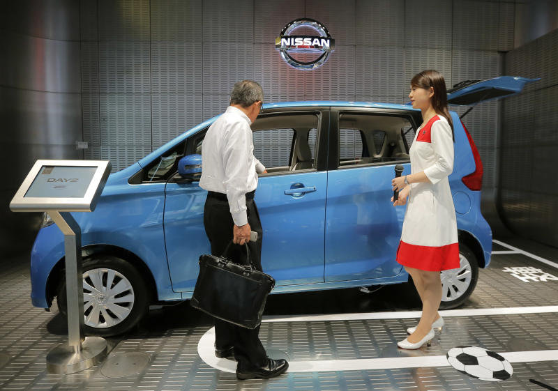 A visitor, left, looks at a Dayz at a Nissan Motor Co., showroom in Tokyo, Tuesday, June 25, 2013. Nissan Chief Executive Carlos Ghosn is promising sales growth to shareholders in a turnaround from years battered by natural disasters and a boycott in China set off by a territorial dispute. Ghosn also told them Tuesday that he earned 9.88 million yen ($9.9 million) for the past fiscal year, up a million yen ($10,000) from the previous fiscal year. (AP Photo/Itsuo Inouye)