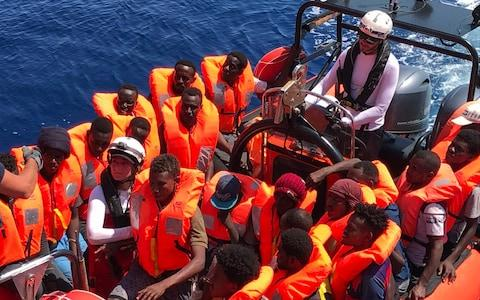 """A """"rhib"""", an inflatable dinghy, belonging to the 'Ocean Viking' rescue ship, operated by French NGOs SOS Mediterranee and Medecins sans Frontieres (MSF), transports rescued migrants - Credit: Anne Chaon/AFP"""