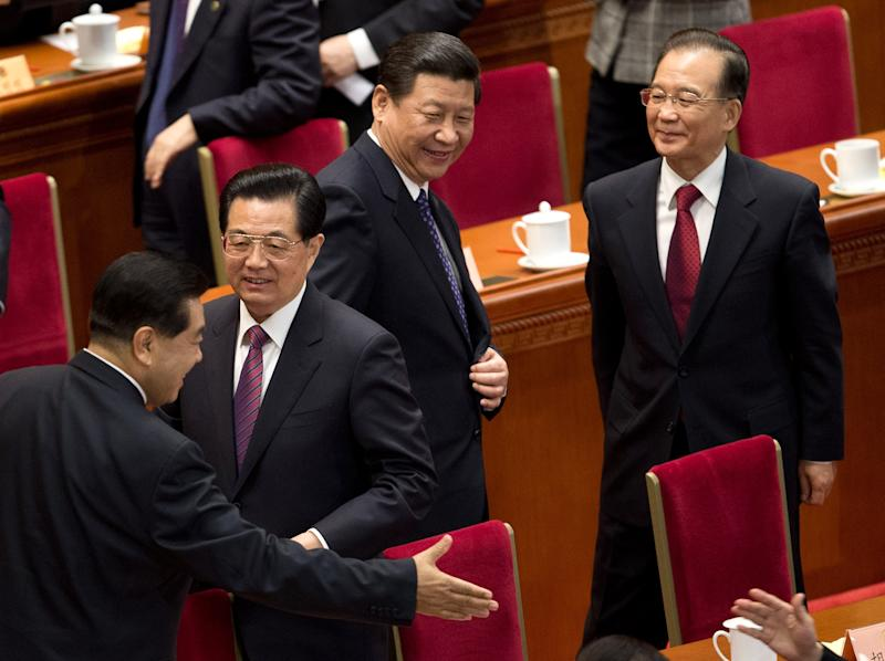 Chinese President Hu Jintao, second from left, Communist Party chief Xi Jinping, center, and Chinese Premier Wen Jiabao, right, look at Jia Qinglin, Chairman of the Chinese People's Political Consultative Conference (CPPCC), left, going to greet a delegate after the opening session of the CPPCC in Beijing's Great Hall of the People Sunday, March 3, 2013. (AP Photo/Andy Wong)