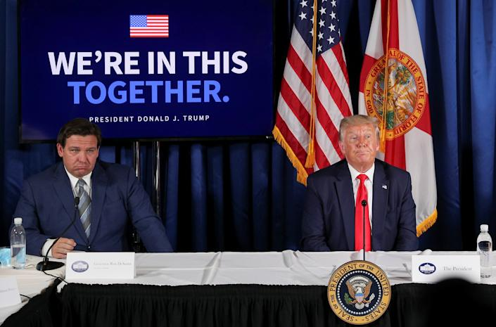 Gov. Ron DeSantis appears to scowl next to Former President Donald Trump at a table with microphones in front of various flags