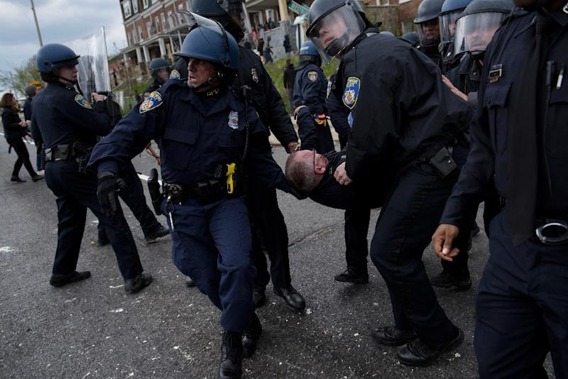 Police officers carry an injured colleague as they clash with protesters in the streets near Mondawmin Mall, in Baltimore, Maryland, on April 27, 2015 (AFP Photo/Brendan Smialowski)