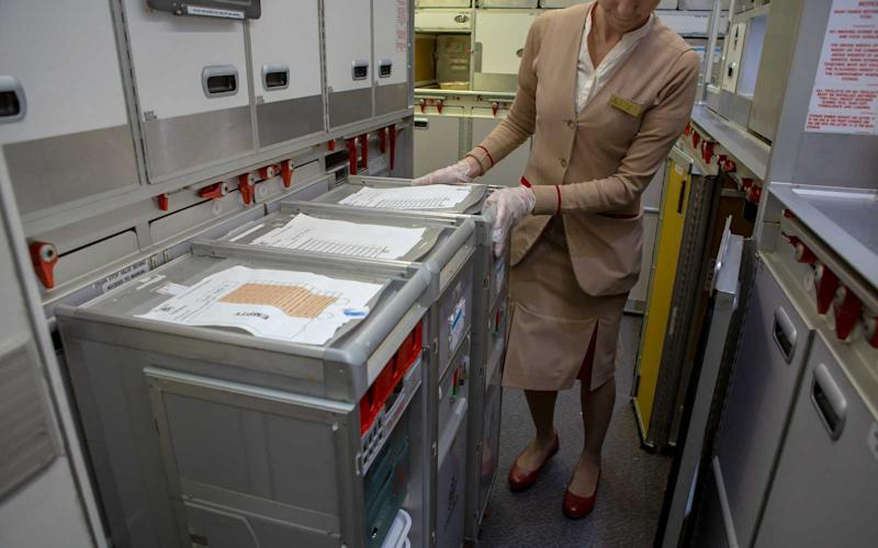 Cabin crew pull out carts to prepare dishes for the breakfast service. | Talia Avakian