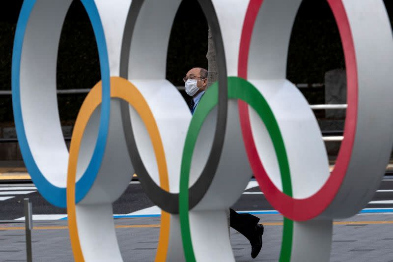 A man wearing a protective face mask, following an outbreak of the coronavirus disease (COVID-19), walks past the Olympic rings in front of the Japan Olympics Museum in Tokyo