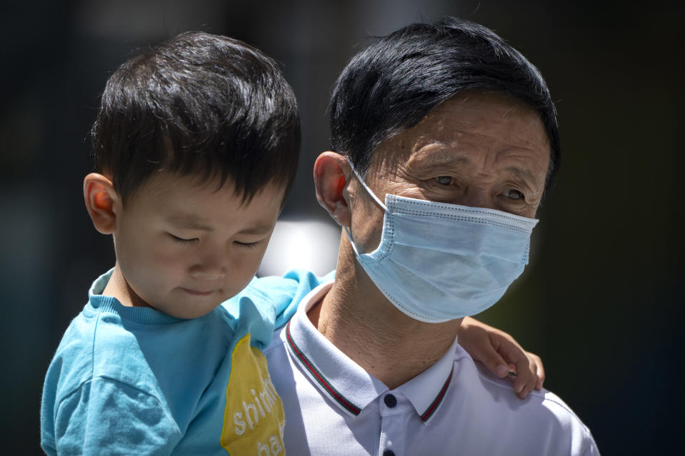A man wearing a face mask to protect against COVID-19 carries a boy as they walk at a shopping and office complex in Beijing, Friday, May 28, 2021. (AP Photo/Mark Schiefelbein)