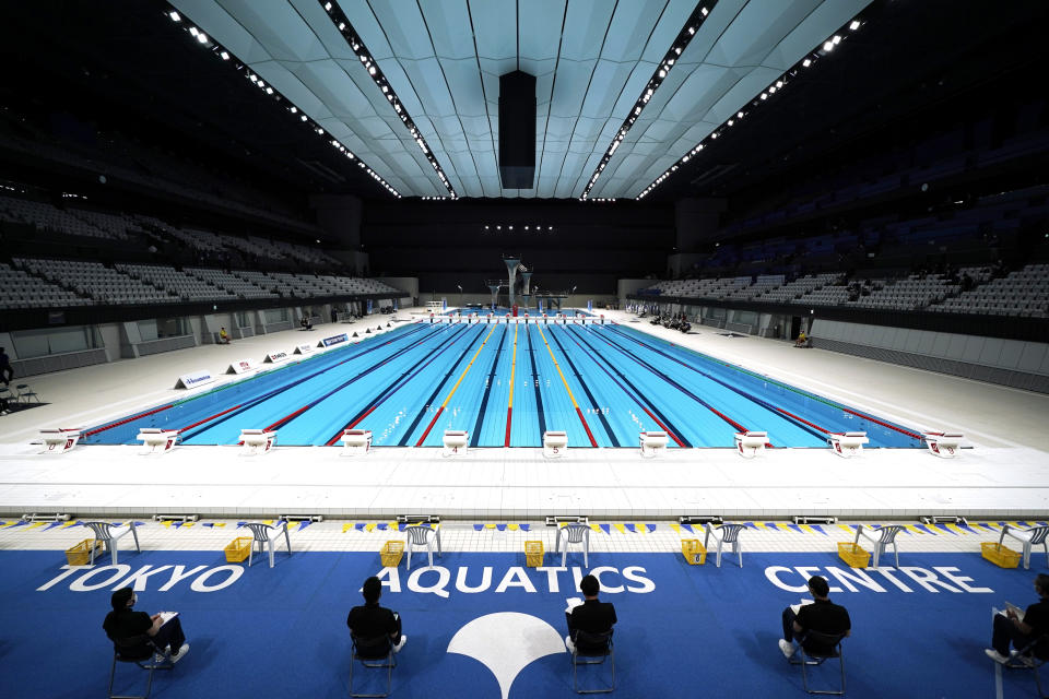 FILE - In this April 26, 2021, file photo, Tokyo 2020 Olympic Games Organizing staff prepare a Paralympic swimming test event at the Tokyo Aquatics Center, one of the venues of the Tokyo 2020 Olympic and Paralympic Games, in Tokyo. Public sentiment in Japan has been generally opposed to holding the Tokyo Olympics and Paralympics. This is partly based of fears the coronavirus will spike as almost 100,000 people — athletes and others — enter for both events.(AP Photo/Eugene Hoshiko, File)