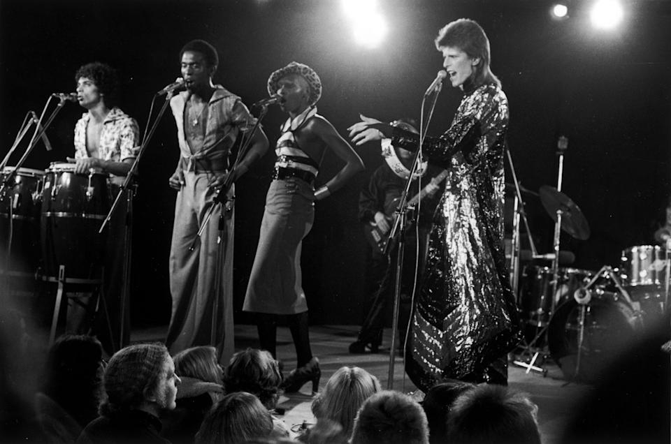 English singer David Bowie (1947 - 2016, right) performing at a live recording of 'The 1980 Floor Show' for the NBC 'Midnight Special' TV show, at The Marquee Club in London' with a specially invited audience of Bowie fanclub members, 20th October 1973. Bowie is wearing a 'space-samurai' costume by Kansai Yamamoto. (Photo by Jack Kay/Daily Express/Hulton Archive/Getty Images)