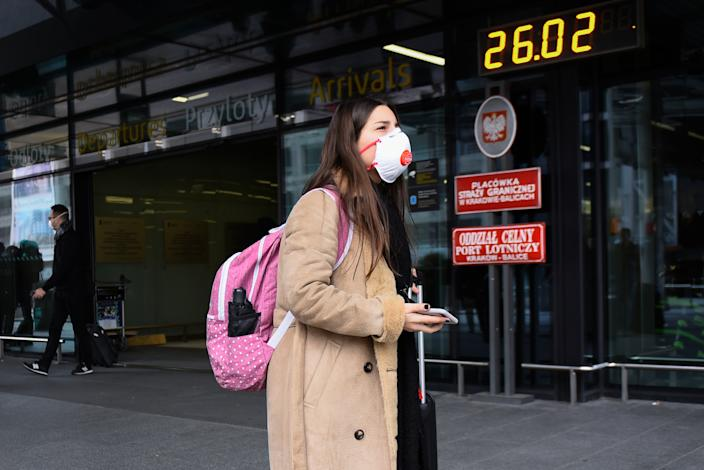 KRAKOW, POLAND - FEBRUARY 26: A passenger wears a surgical mask after landing at Krakow International Airport on February 26, 2020 in Krakow, Poland. As five European countries have reported cases of Covid-19 linked to Italy, medical checks are being implemented on all flights arriving from Northern Italy to Poland. According to the World Health Organization (WHO) more than 81,000 people have been diagnosed and around 2700 have died due to the Coronavirus outbreak. (Photo by Omar Marques/Getty Images)