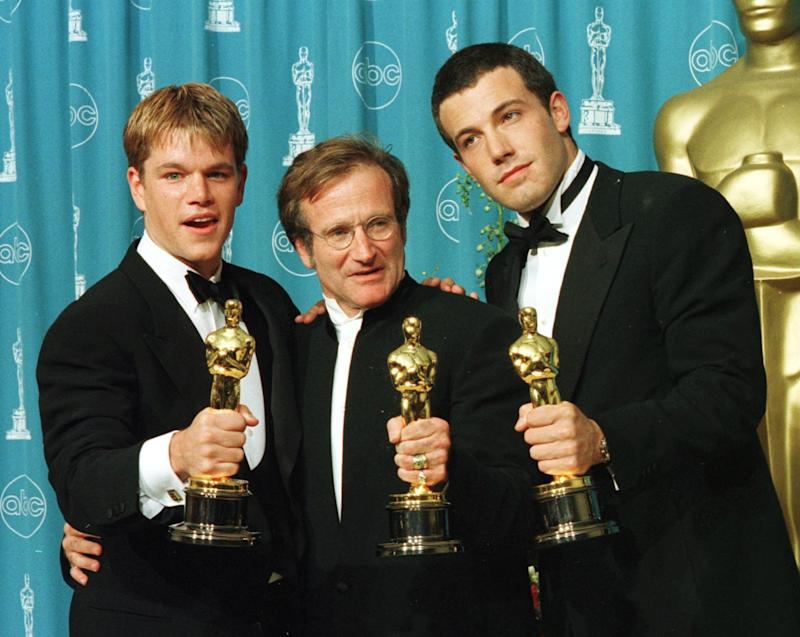 """Actors-writers Matt Damon (L) and Ben Affleck (R) pose with actor Robin Williams with their Oscars they won for """"Good Will Hunting"""" at the 70th Annual Academy Awards 23 March in Los Angeles. Damon and Affleck won Best Original Screenplay and Williams won for Best Supporting Actor. AFP PHOTO/Hal GARB (Photo by HAL GARB / AFP) (Photo by HAL GARB/AFP via Getty Images)"""