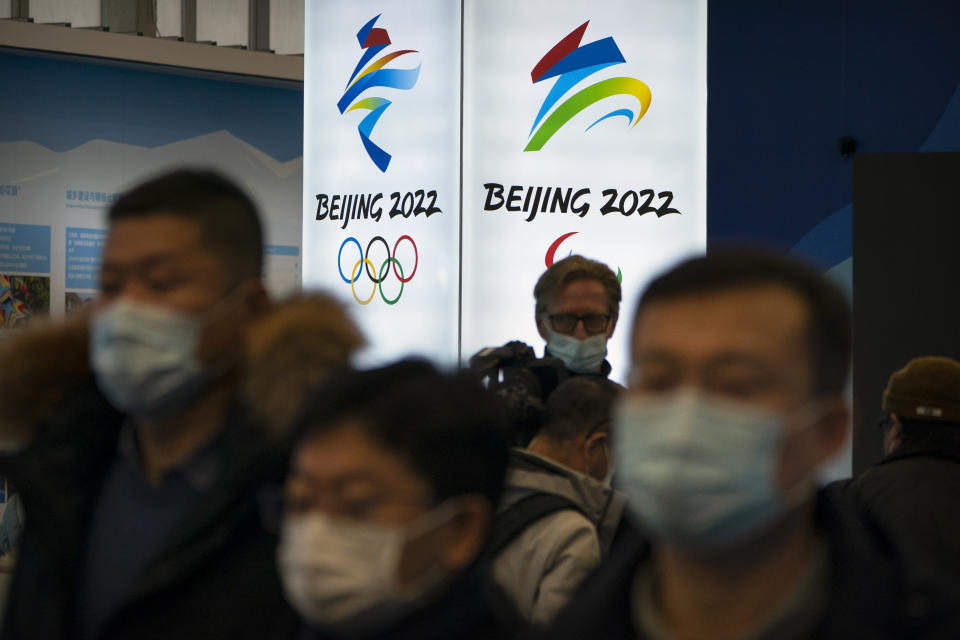 Attendees wearing face masks to protect against the spread of the coronavirus look at an exhibit at a visitors center at the Winter Olympic venues in Yanqing on the outskirts of Beijing, Friday, Feb. 5, 2021. Beijing Olympic organizers showed off the downhill skiing venue and the world's longest bobsled and luge track Friday, one year ahead of the scheduled opening of the 2022 Olympic Winter Games. (AP Photo/Mark Schiefelbein)