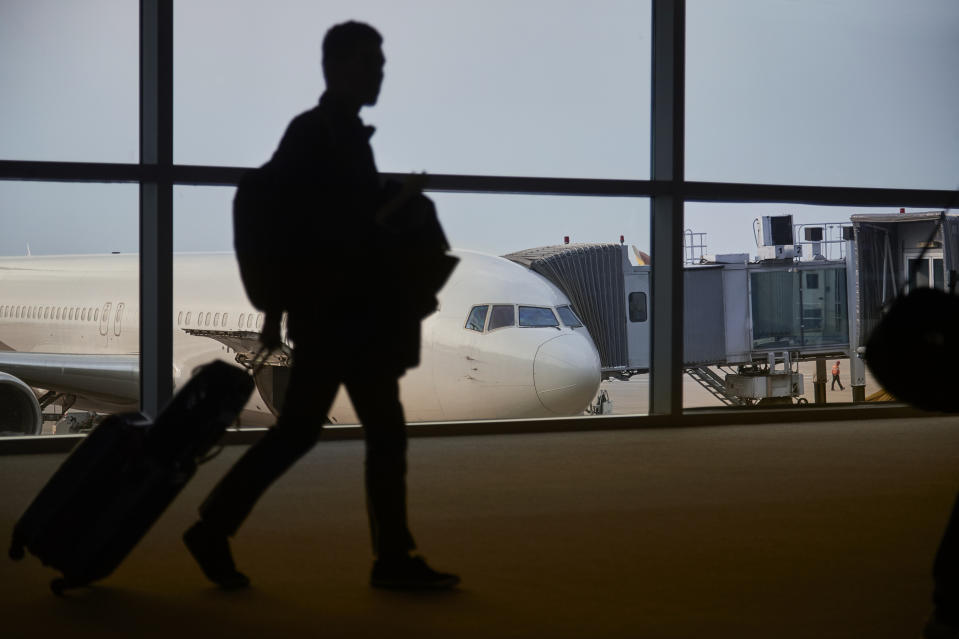 A passenger is in the shadow walking past a commercial aircraft docked to an airport terminal