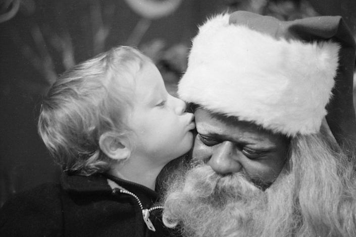 <p>During the Christmas retail season, a young white boy kisses a Black Santa Claus on the cheek in an unidentified department store.</p>