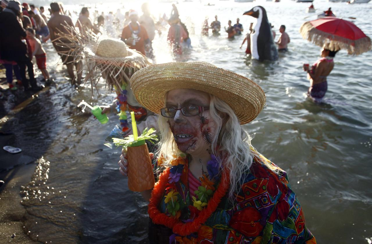 A participant dressed as a zombie walks out of the water after running into English Bay during the 95th annual New Year's Day Polar Bear Swim in Vancouver, British Columbia January 1, 2015. REUTERS/Ben Nelms (CANADA - Tags: SOCIETY ENVIRONMENT ANNIVERSARY)
