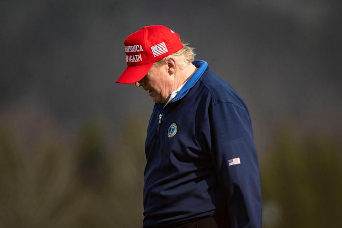 <p>Donald Trump, pictured playing golf on Sunday, retweeted a message accusing Joe Biden of 'pretending' to win the election</p> (Getty Images)