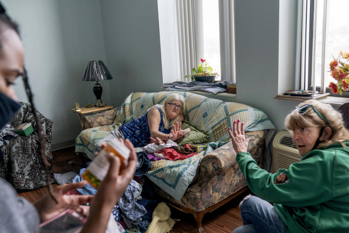 Sue Howland, right, and Larrecsa Cox, left, members of the Quick Response Team whose mission is to save every citizen who survives an overdose from the next one, help Betty Thompson, 65, who struggles with alcohol addiction, count her medications at her apartment in Huntington, W.Va., Wednesday, March 17, 2021. Thompson called that morning to say she needed help. With preexisting conditions that make her especially vulnerable to COVID, she'd been terrified she'd get the virus and die, and so she's drank more these months than she ever has before. (AP Photo/David Goldman)