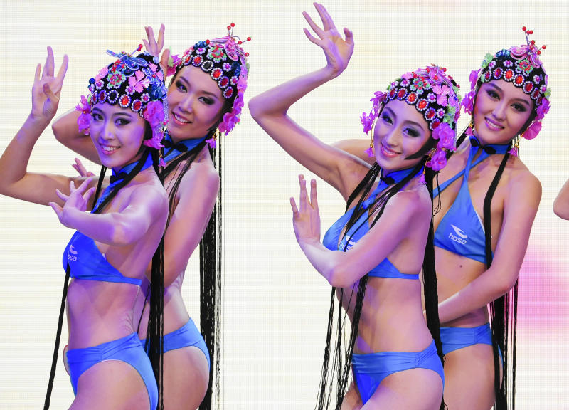 In this undated photo released by Miss Bikini International Committee on Thursday, Sept. 27, 2012, contestants in swimwears and traditional Chinese opera headpieces dance during an rehearsal for their up-coming bikini competition in Beijing. A stage performance by bikini-clad women wearing headpieces styled after traditional Peking Opera has sparked debate in China after photos were made public this week, highlighting divided views on how to preserve the country's traditions. (AP Photo/Miss Bikini International Committee) EDITORIAL USE ONLY, NO SALES