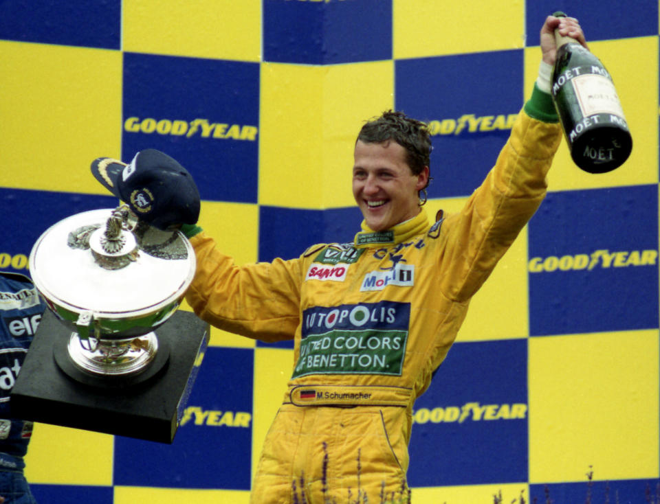 FILE - In this Aug. 30, 1992 file photo, German Formula One racing driver Michael Schumacher holds the trophy and magnum bottle of champagne, after winning his first Grand Prix race in Francorchamps, Belgium. British driver Lewis Hamilton made Formula One history on Sunday, Oct. 25, 2020 winning the Portuguese Grand Prix for a 92nd win to move one ahead of German great Michael Schumacher. (AP Photo/Roberto Pfeil, file)