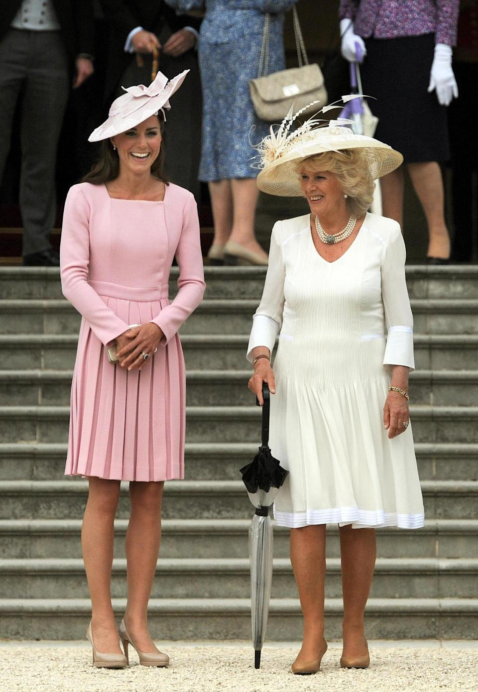 <p>Kate wore a familiar pink pleated dress by Emilia Wickstead for a garden party at Buckingham Palace. She accessorised with a wide-brimmed hat by Jane Corbett and donned a bag and heels from L.K. Bennett.</p><p><i>[Photo: PA]</i></p>
