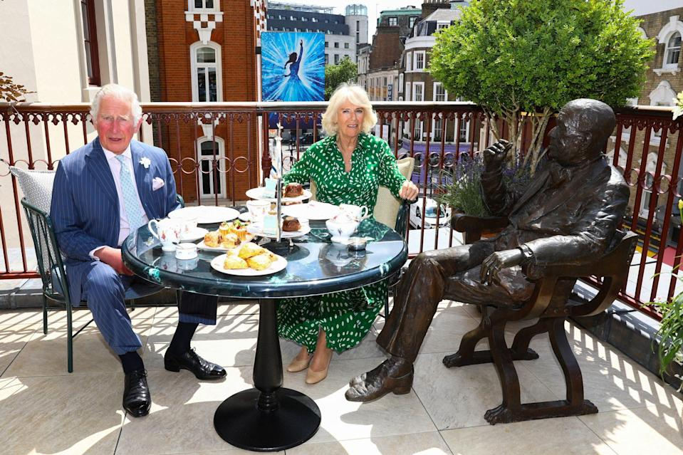<p>Prince Charles and Camilla, Duchess of Cornwall enjoy afternoon tea beside a statue of playwright Nöel Coward during a visit to Theatre Royal on June 23 in London.</p>