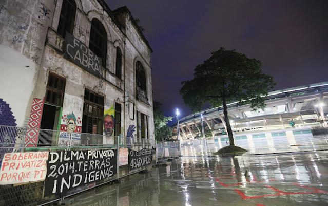 RIO DE JANEIRO, BRAZIL - OCTOBER 17: The Aldeia Maracana building (L) being occupied by an indigenous community stands next to Maracana Stadium (R), the site of the 2014 World Cup finals, on October 17, 2013 in Rio de Janeiro, Brazil. The fading Aldeia Maracana used to house the Museum of Indian Culture before deteriorating and becoming occupied by squatting indigenous members in 2006. The building was slated for destruction ahead of the 2014 World Cup and the community was forcibly evicted in March. However, the community has managed to return and thus far have successfully battled to save the structure, which they hope to convert into an indigenous university. Indigenous groups throughout Brazil are battling the Brazilian government over land rights and other issues. (Photo by Mario Tama/Getty Images)