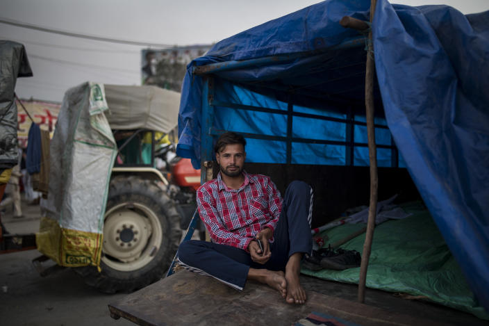 Farmer Sikandar Machhonda, 22, sits at the back of his tractor trailer parked on a highway in a sign of protest against new farm laws, at the Delhi-Haryana state border, India, Wednesday, Dec. 2, 2020. The convoy of trucks, trailers and tractors stretches for at least three kilometers (1.8 miles). Inside, they have hunkered down, supplied with enough food and fuel to last weeks. (AP Photo/Altaf Qadri)