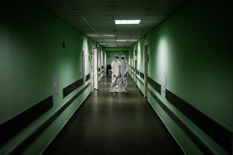 Medical workers wearing personal protective equipment (PPE) stand in a hall of Vinogradov City Clinical Hospital, which delivers treatment to coronavirus patients, in Moscow on May 17, 2020