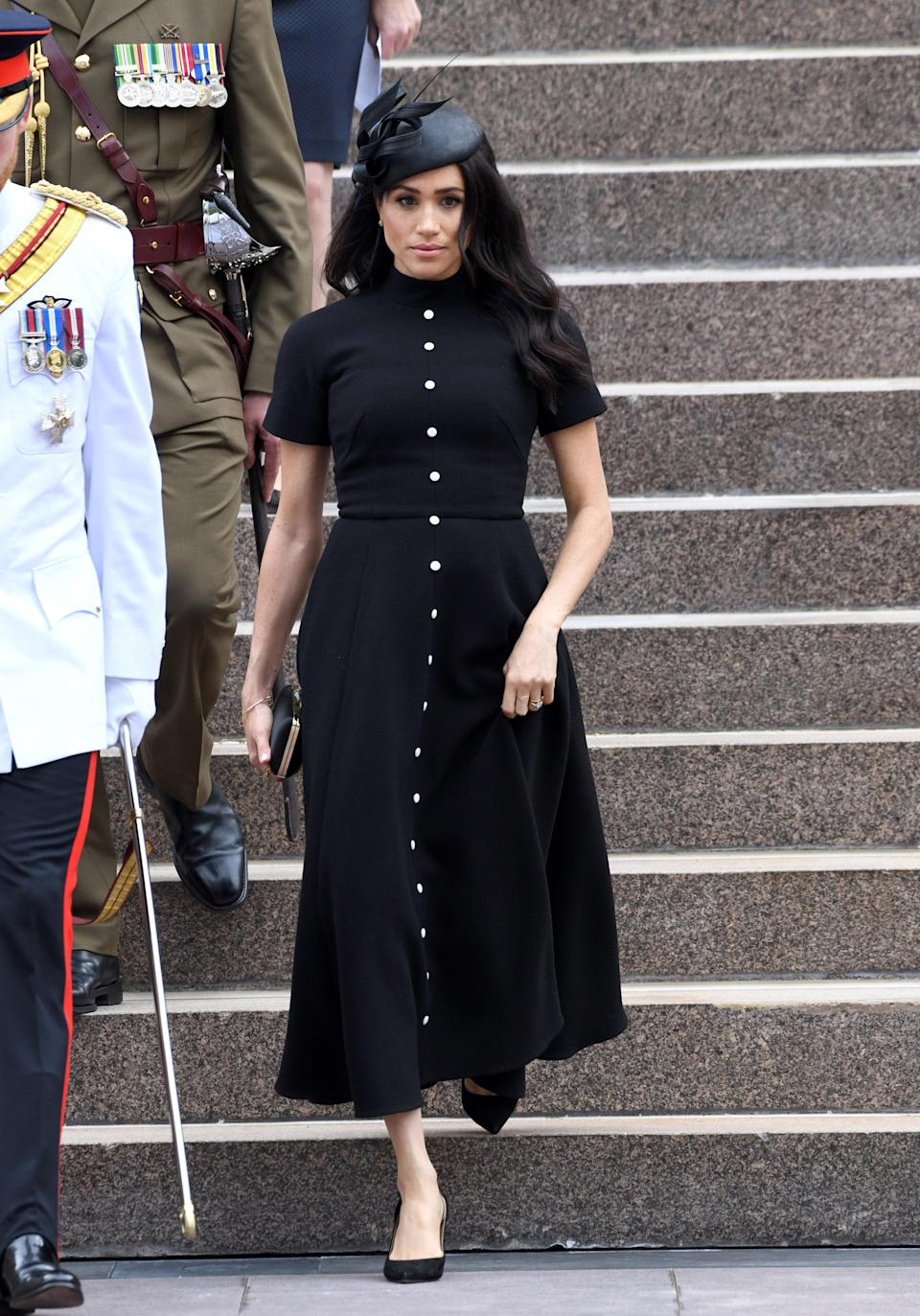 <p>Meghan wore a custom made black Emilia Wickstead dress with a Philip Treacy hat, a satin Givenchy clutch and Tabitha Simmons slingback pumps for the official opening of the extension of the ANZAC Memorial in Hyde Park in Sydney, Australia. <em>[Photo: Getty]</em> </p>